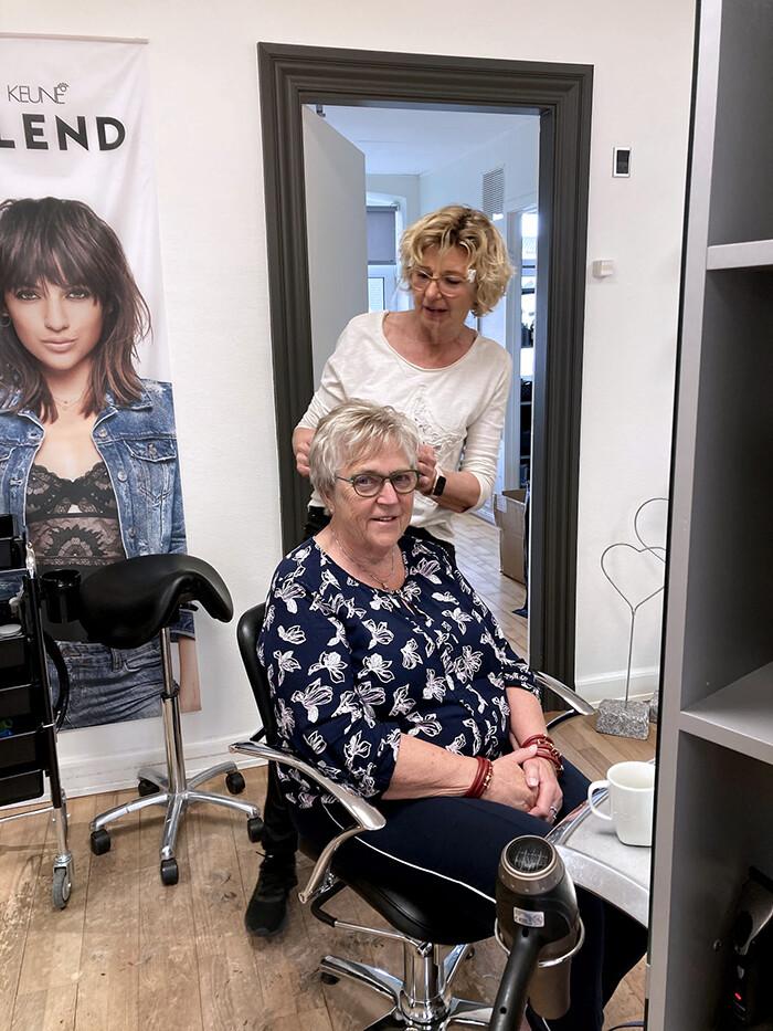 Jette Lykke Christensen lod lokkerne falde hos Salon Sanne. Her ses Sanne Vesperini i gang med at klippe hendes hår. Foto Ingrid Johannsen